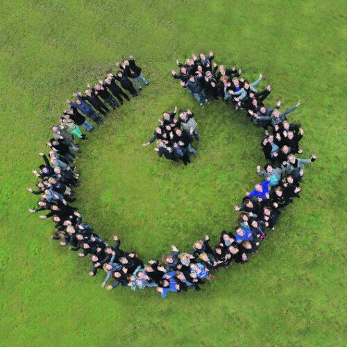 Aus der Luft fotografiert, formt eine Menschenmenge auf Rasen stehend das Logo der Lebenshilfe.